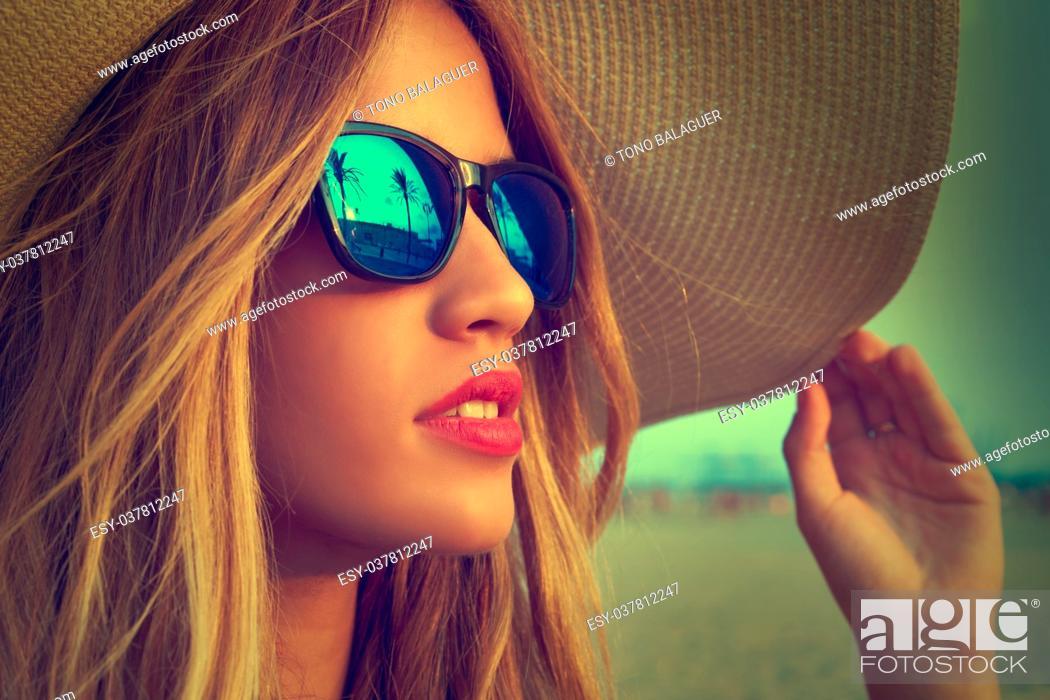 Imagen: Blond teen girl sunglasses and pamela sun hat at palm tree sunset filtered image.