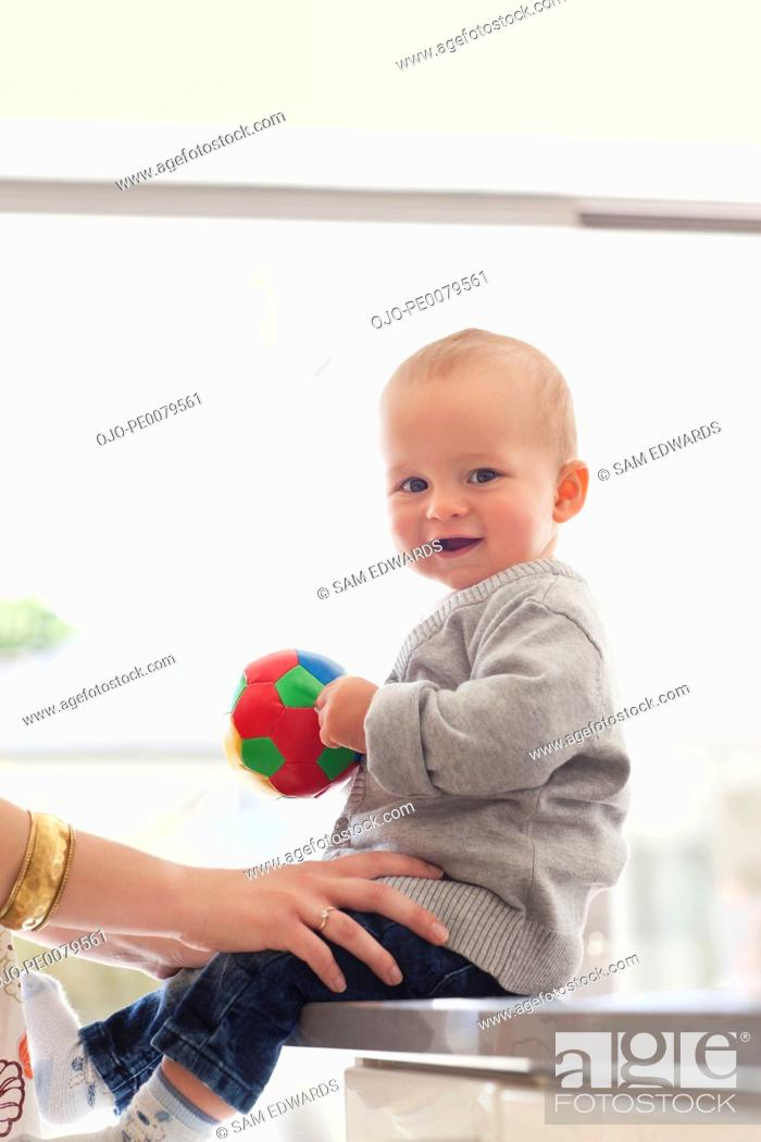 Stock Photo: Smiling baby holding ball.