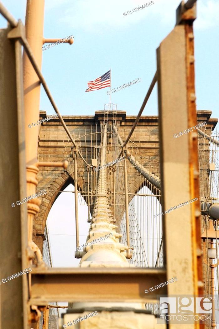 Stock Photo: Low angle view of an American flag on a bridge, Brooklyn Bridge, New York City, New York State, USA.