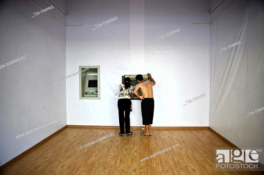 Stock Photo: A man and a woman take money from an ATM austere. China.