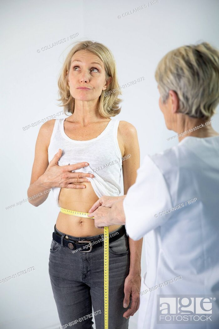 Stock Photo: A woman measuring her waist.