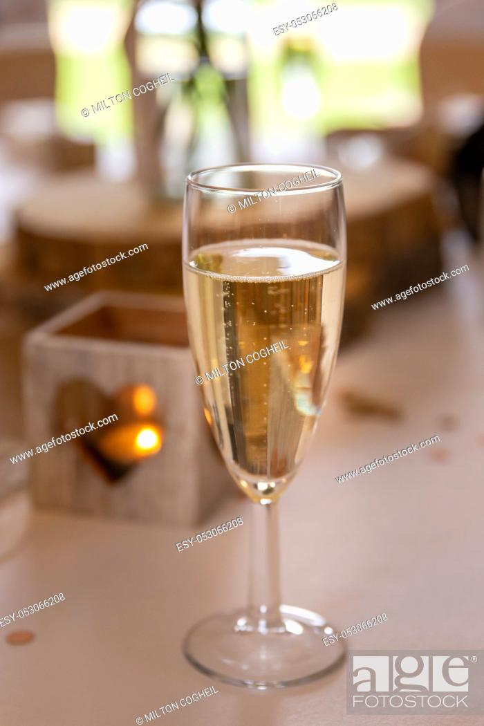 Stock Photo: Love concept. Champagne glass with heart shaped candle holder in a wedding setting.