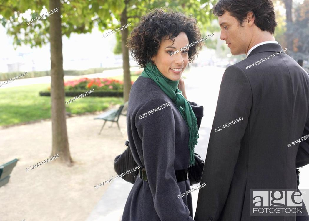 Stock Photo: Couple standing outdoors holding hands smiling.