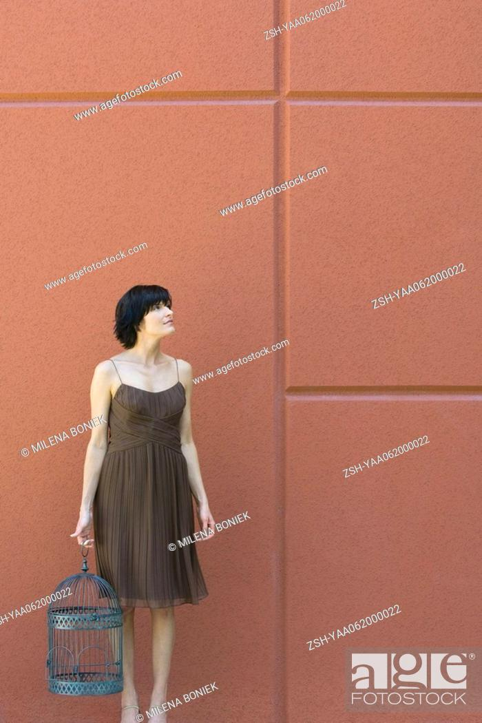 Stock Photo: Woman standing, holding empty bird cage, looking up.