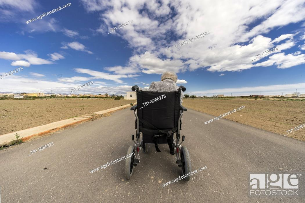 Stock Photo: Old woman in wheelchair on the middle of a road.
