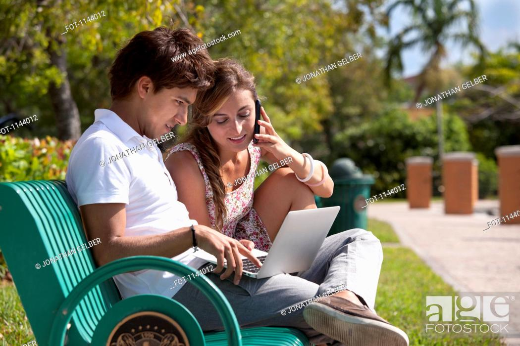 Stock Photo: A young couple sitting on a park bench using a laptop and mobile phone.