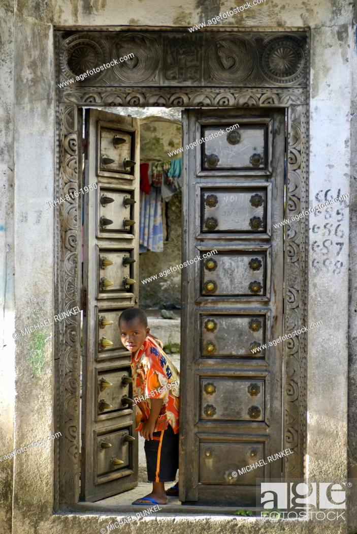 Stock Photo: Young boy curiously looking through an old antique door, Moroni, Grand Comore, Comores, Indian Ocean, Africa.