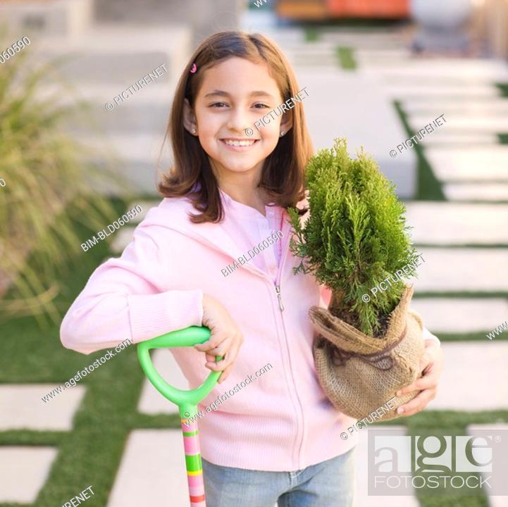 Stock Photo: Hispanic girl holding tree in burlap.