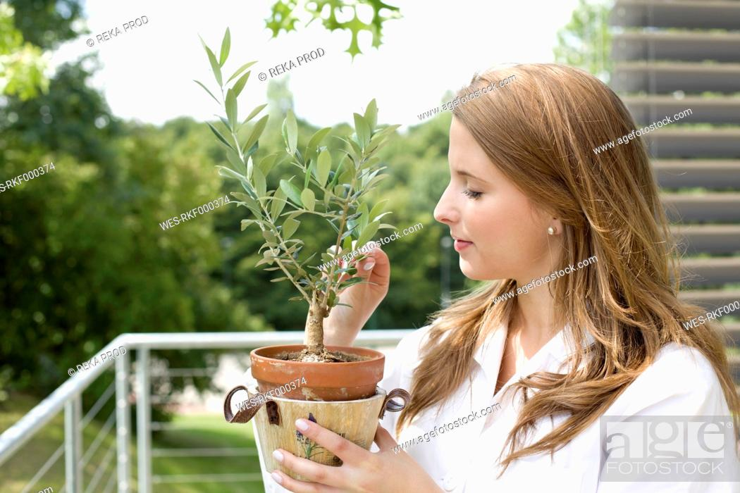 Stock Photo: Europe, Germany, North Rhine Westphalia, Duesseldorf, Young student smelling pottted plant.