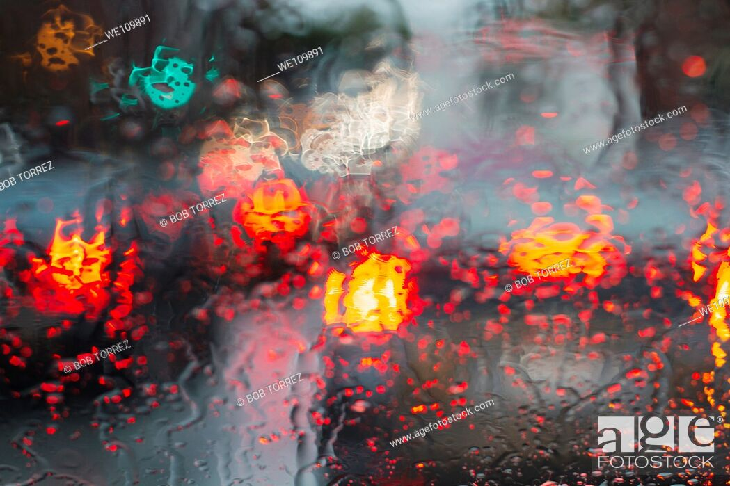 Stock Photo: Drivers view of city traffic through rain drenched windshield.