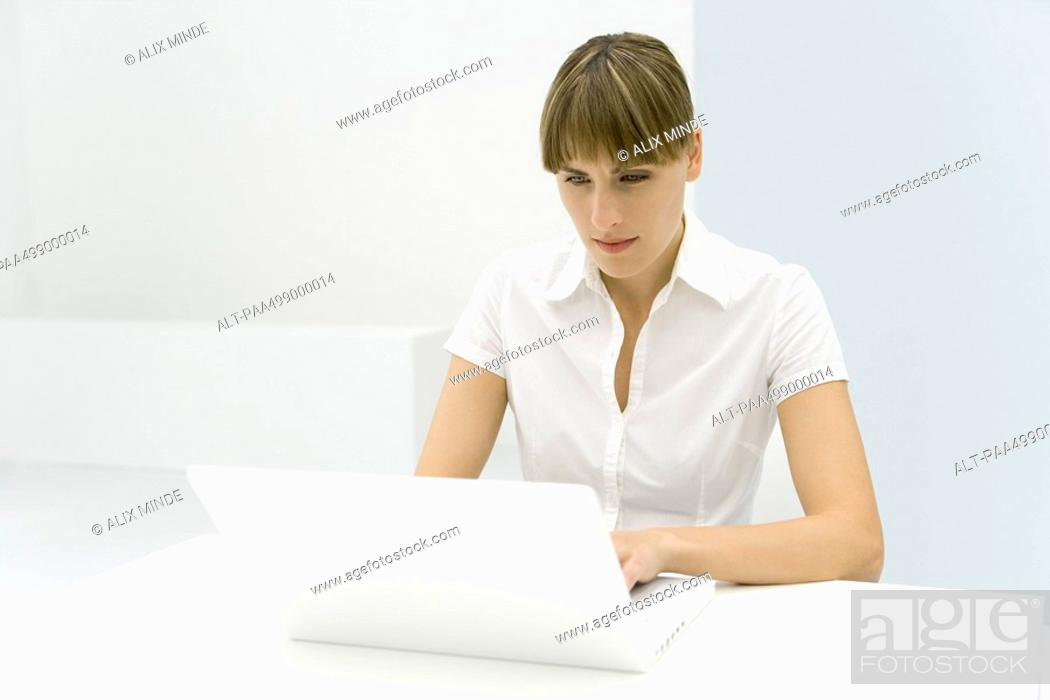 Stock Photo: Woman using laptop computer, furrowing brow.