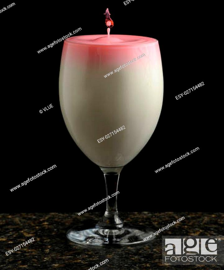 Stock Photo: Drop of liquid suspended above a glass full of creamy blended cocktail with a pink surface isolated on a black background.