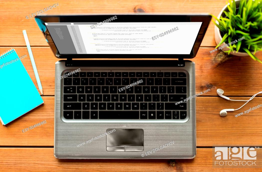 Stock Photo: programming, education, business and technology concept - close up of laptop computer with coding on screen on wooden table.