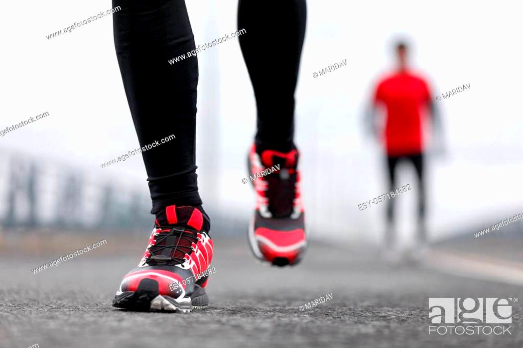 Imagen: Running shoes - closeup of male runners running on winter street. Sport fitness athlete man jogging outdoors on city road in cold weather.