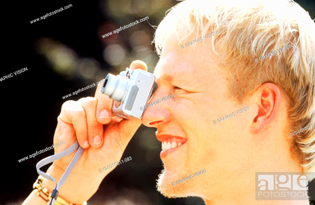 Stock Photo: Side profile of a young man taking photographs with a camera.