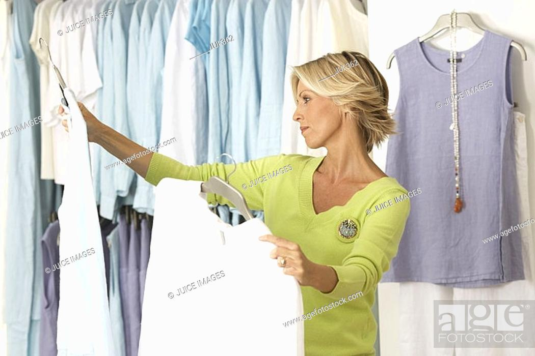Stock Photo: Mature woman shopping in clothes shop, comparing two tops on coathangers, side view.