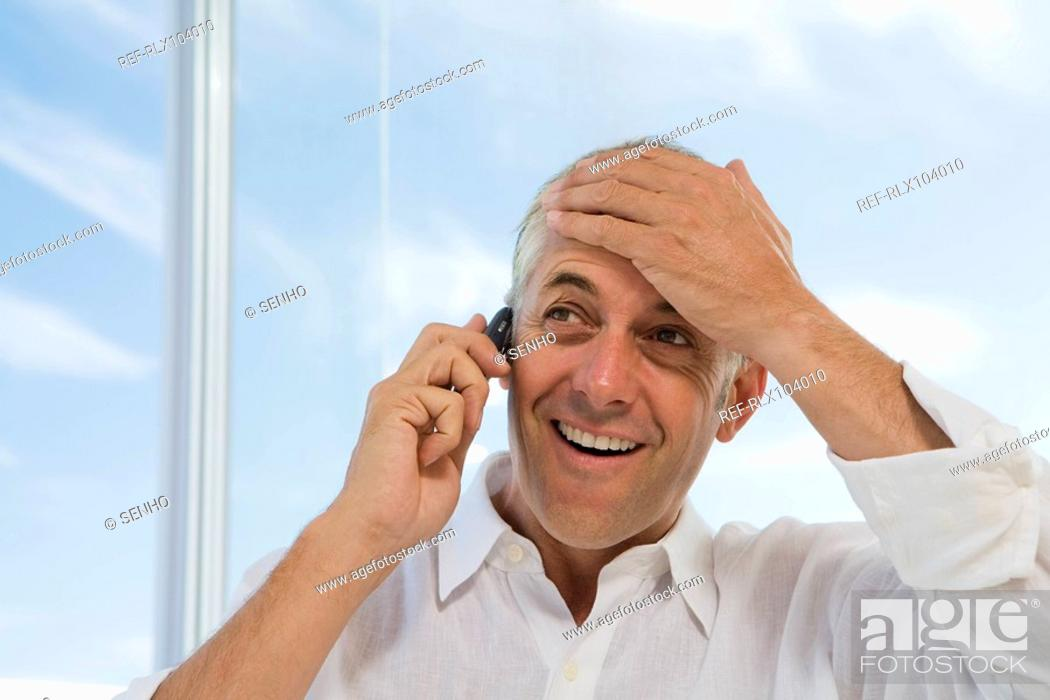 Stock Photo: Mature man at window smiling, using cell phone, holding hand to head.