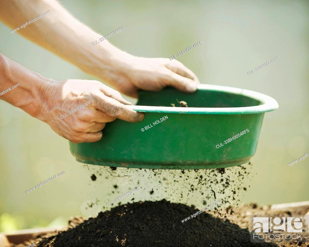 Stock Photo: Hands sifting soil outdoors.