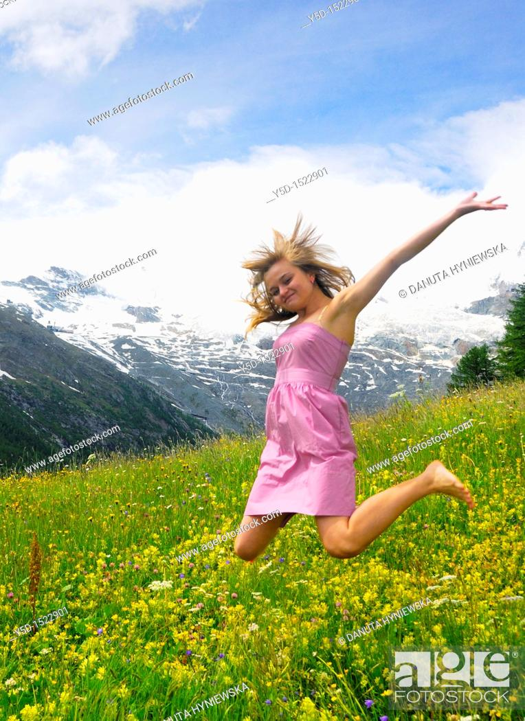 Stock Photo: young woman jumping in the mountains, Saas Fee, canton Valais, Switzerland.