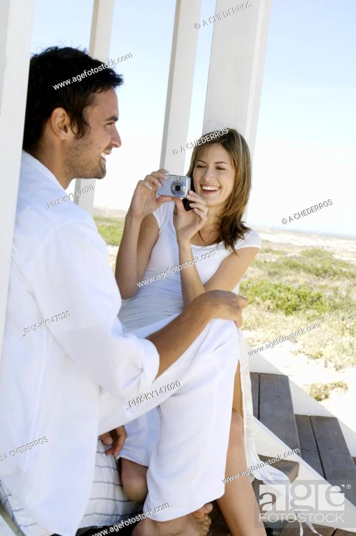 Stock Photo: Smiling woman photographing man on wooden terrace.