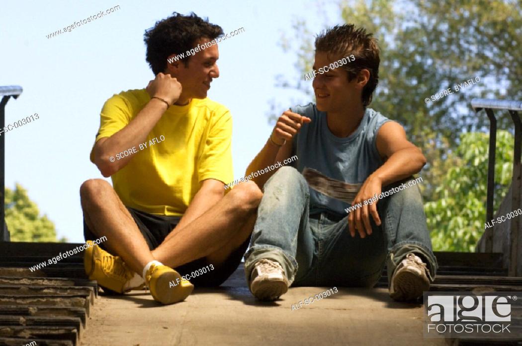 Stock Photo: Teenage boys chatting on steps.