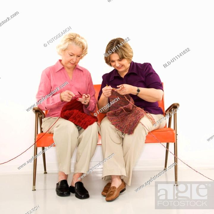 Stock Photo: Caucasian middle aged woman and senior woman sitting and knitting.