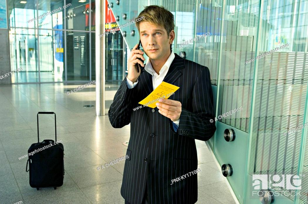 Stock Photo: Businessman holding an airplane ticket and talking on a mobile phone.