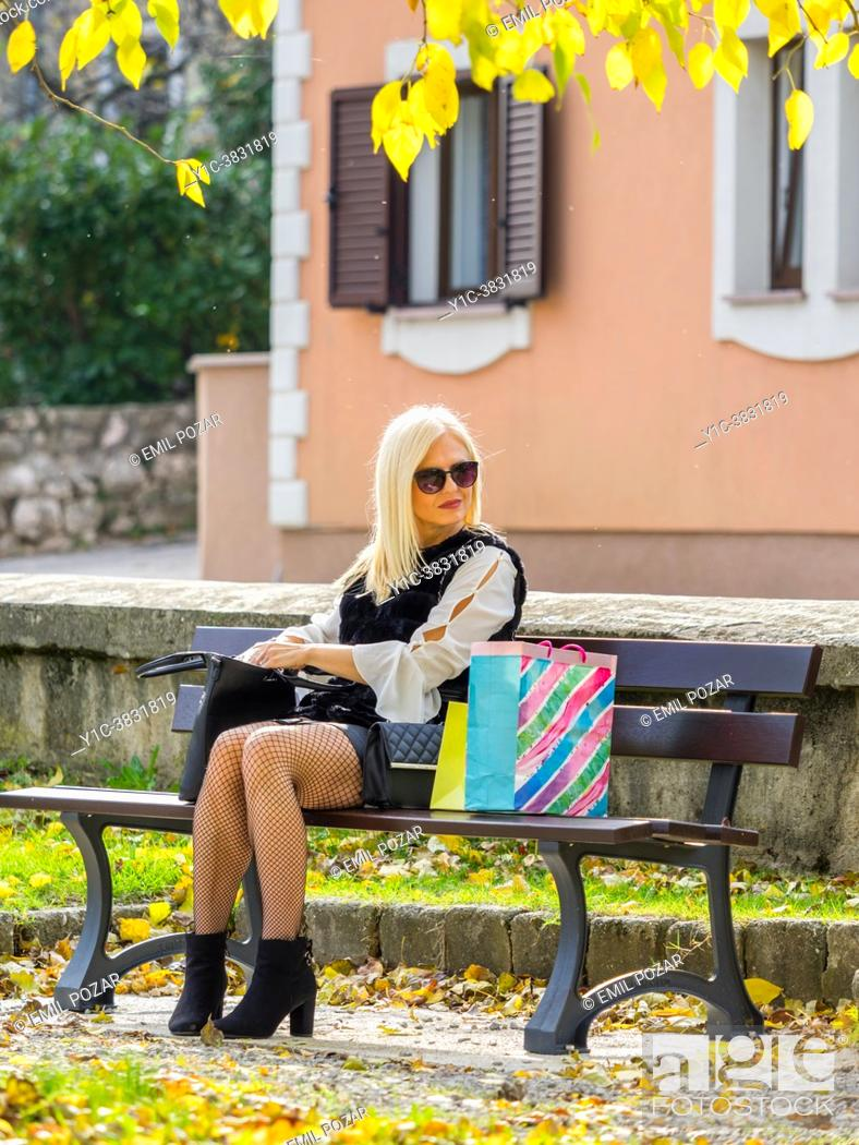 Stock Photo: Attractive shopper woman in park with shopping bags is searching in handbag.