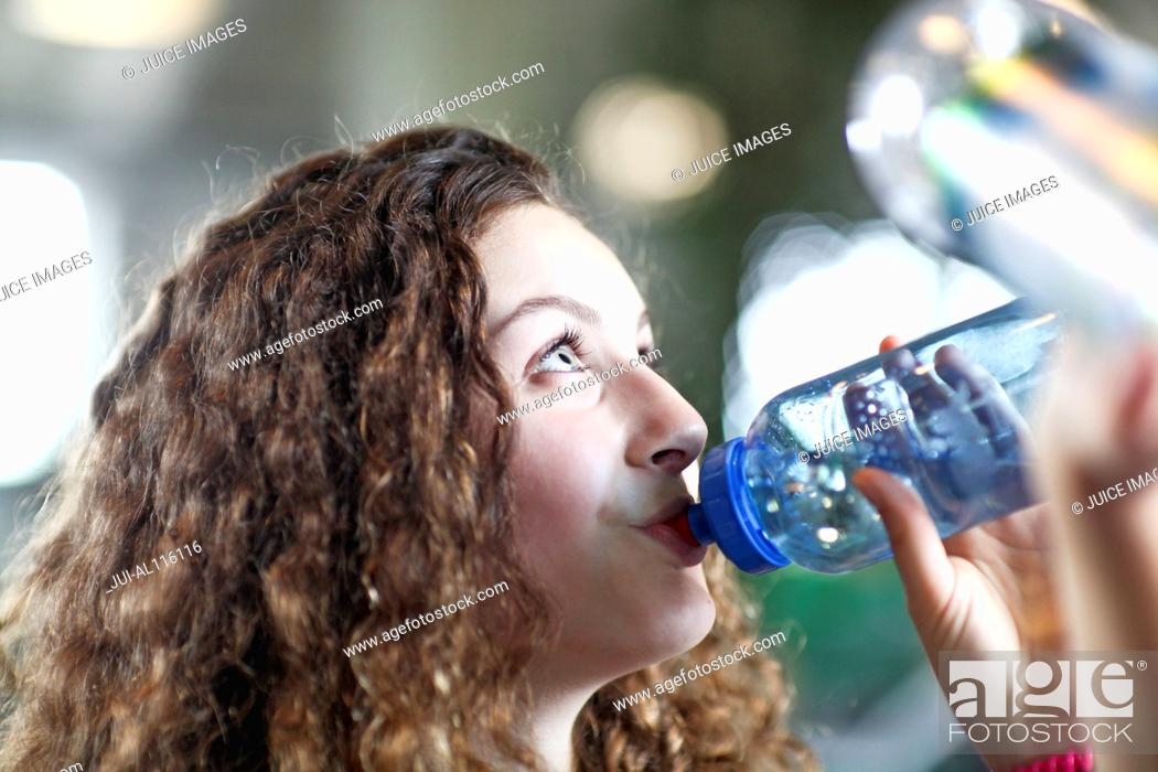 Stock Photo: Teenage girl drinking from water bottle in gym.