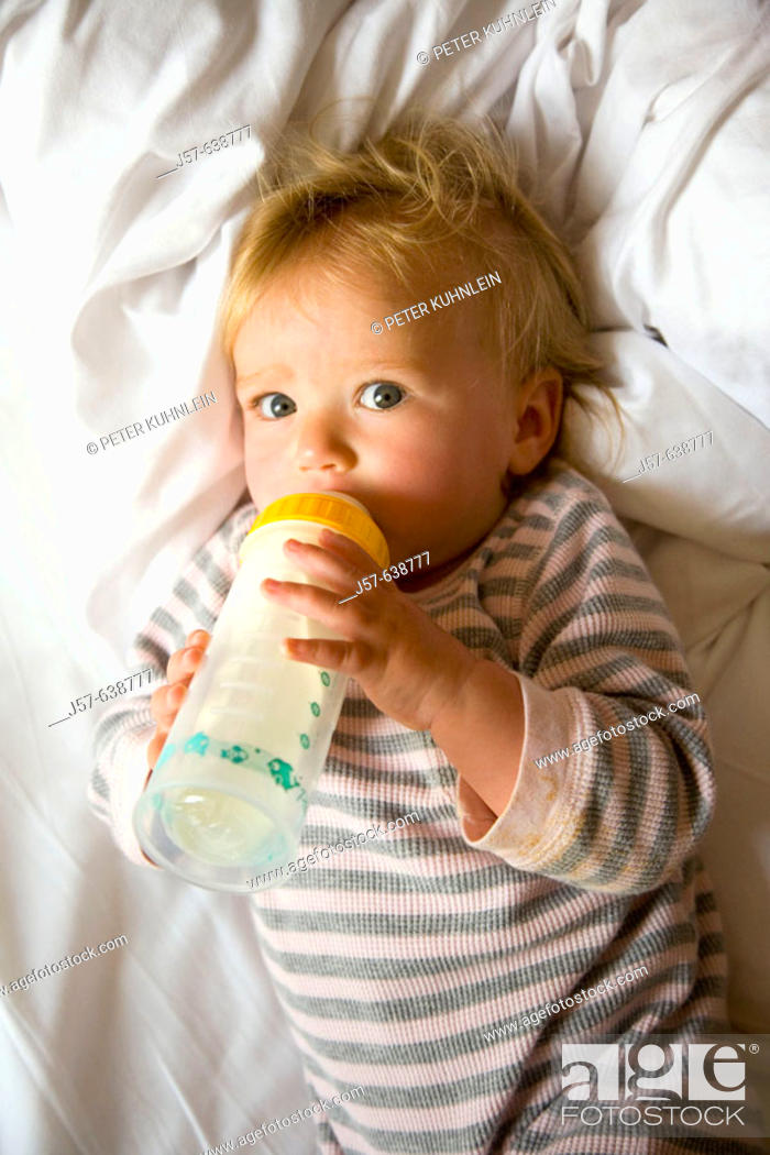 Stock Photo: 16 month old baby girl drinking a bottle of milk in the morning.