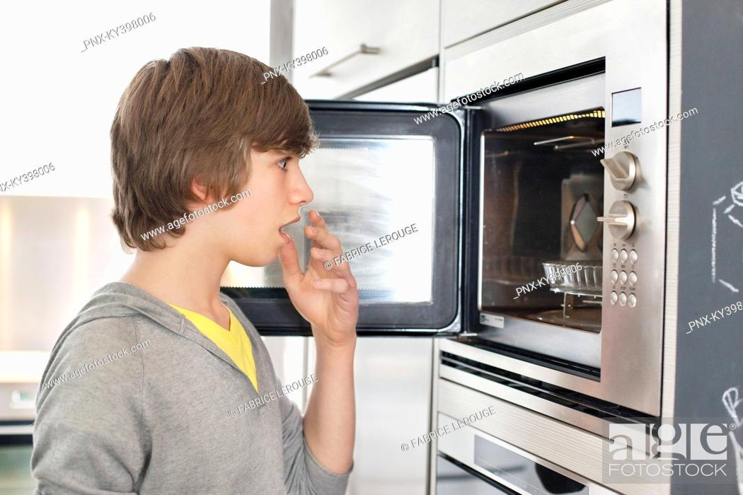Stock Photo: Teenage boy looking into an oven with surprise.