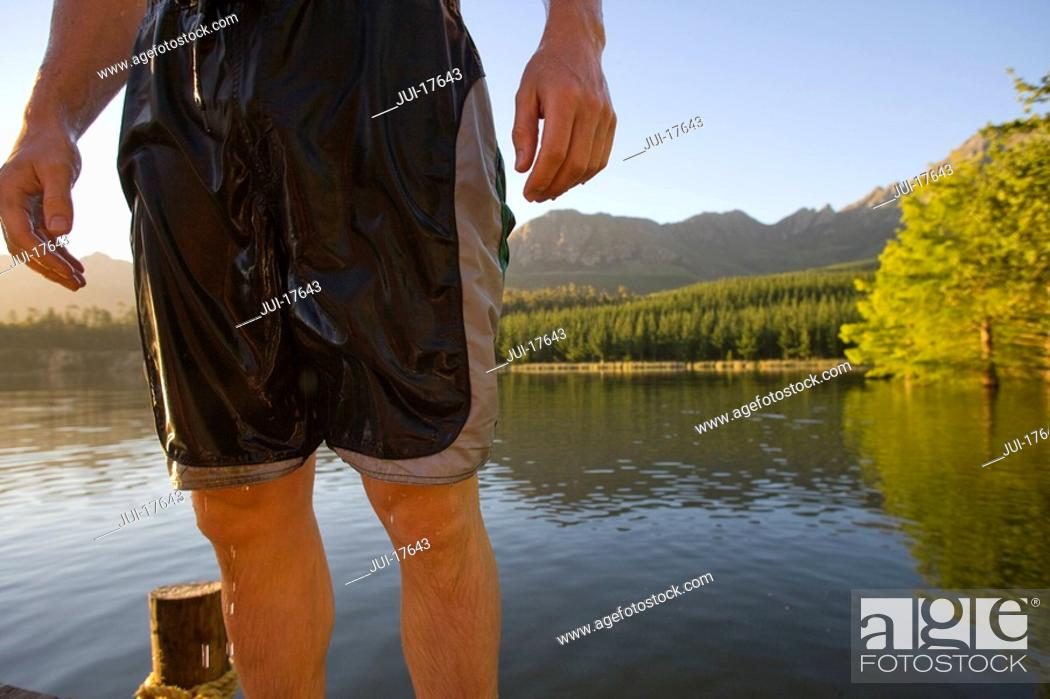 Stock Photo: Midsection of man in wet swim trunks.