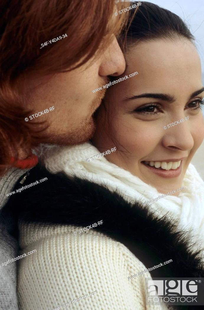 Stock Photo: Young darkhaired Woman leaning against the Chest of an auburn haired Man - Togetherness - Relationship - Tenderness.