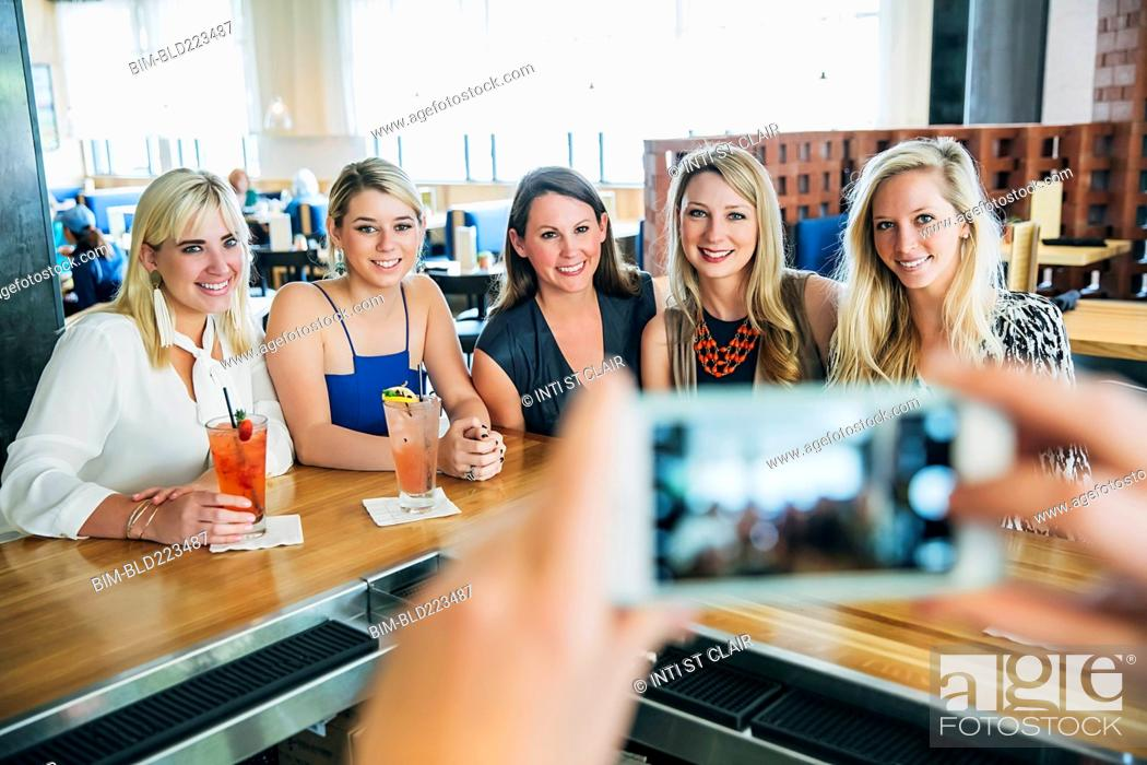 Stock Photo: Caucasian bartender taking cell phone photograph of customers.