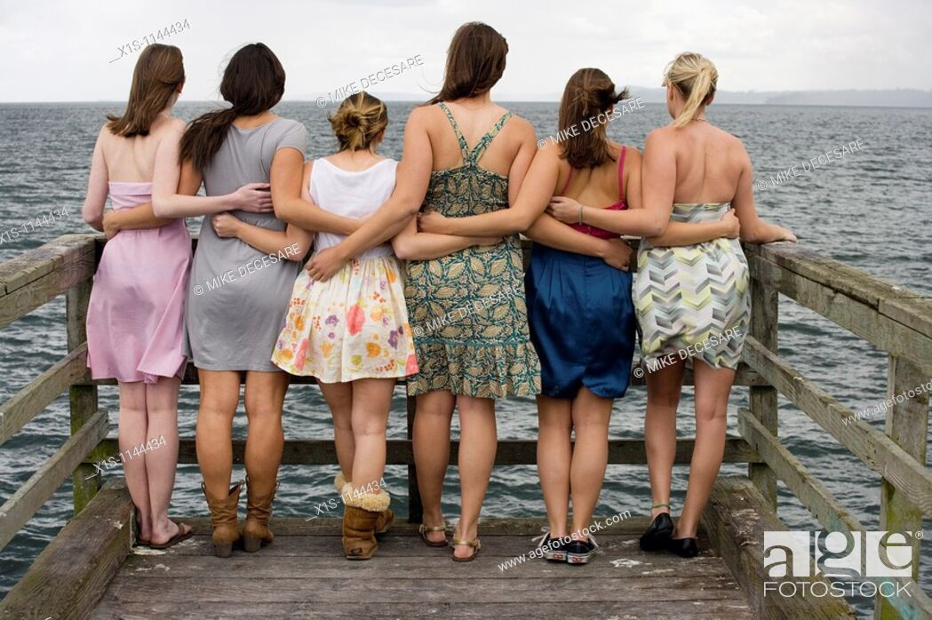 Stock Photo: At the end of a pier, six young women with their backs to the camera are connected by arms as they look out into the water.