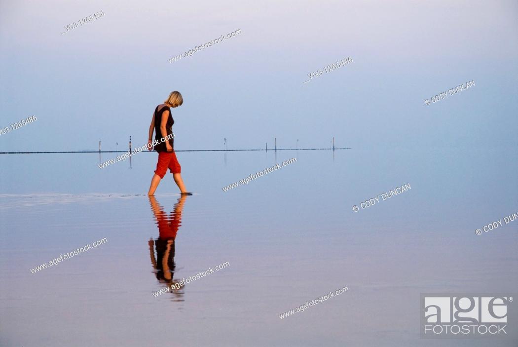 Stock Photo: Reflection of woman walking in Wadden sea, Juist, Germany.