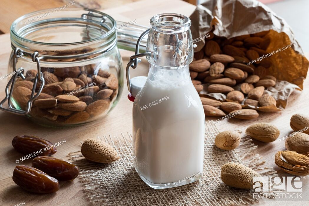 Stock Photo: A bottle of almond milk with whole (unshelled) and shelled almonds and dates.