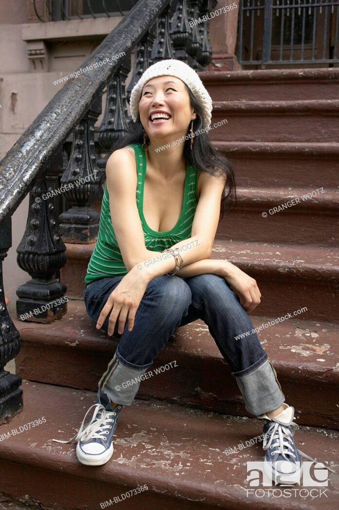 Stock Photo: Asian woman sitting on front steps.