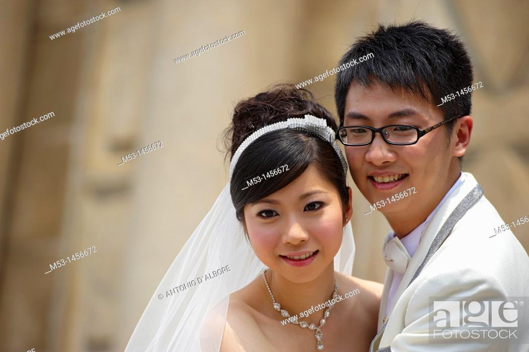 Stock Photo: Young chinese bride and grrom posing for a picture.