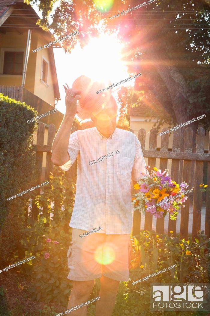 Stock Photo: Senior man in garden, holding bunch of fresh cut flowers.