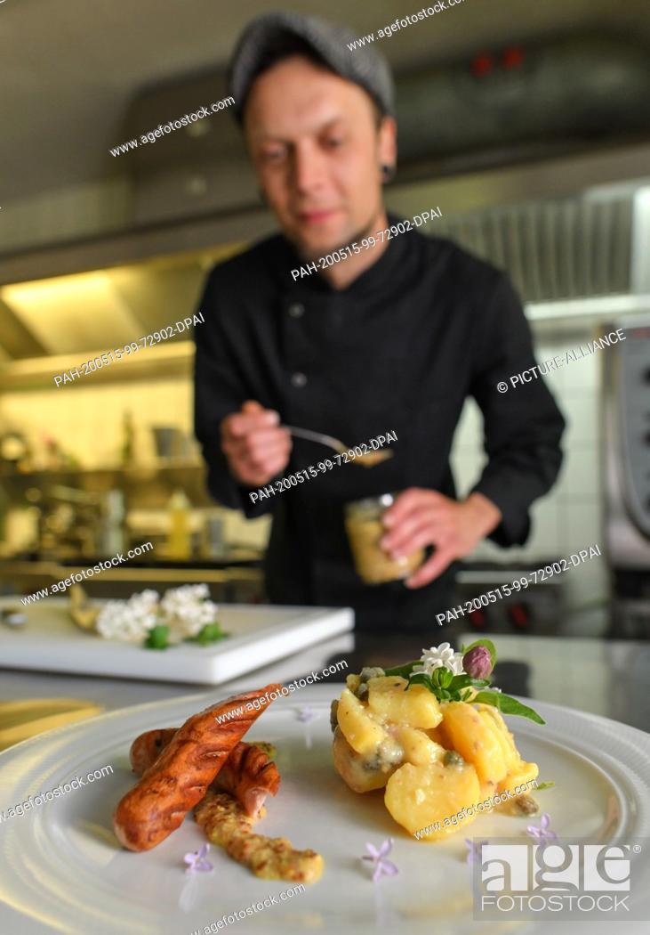 Stock Photo: 15 May 2020, Brandenburg, Kaisermühl: Sören Horny, cook at Hotel Kaisermühle, prepares a wild garlic sausage with potato caper salad in the kitchen.