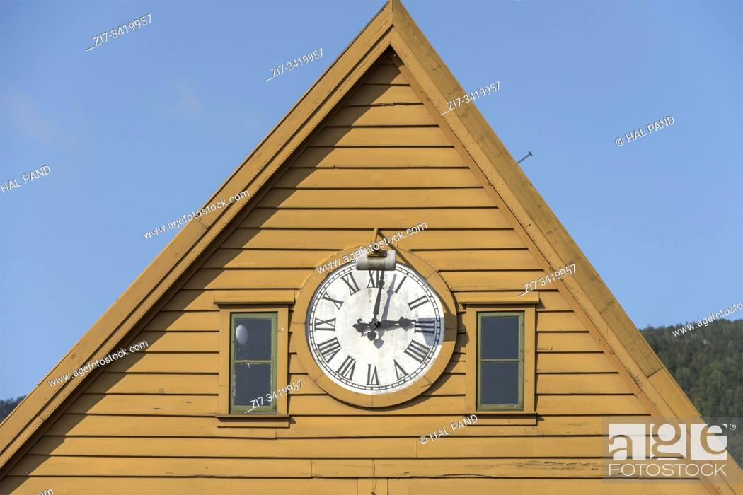 Stock Photo: cityscape with wall clock on picturesque colorful facade on Briggen neighborhood quay, shot under bright summer light at Bergen, Norway.