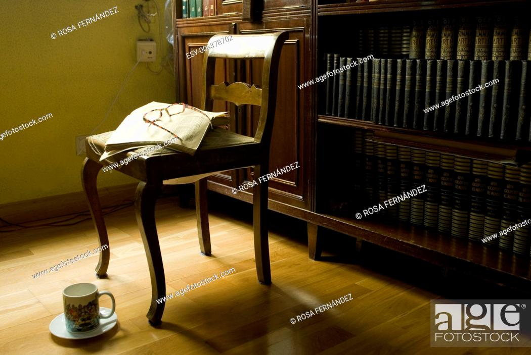 Stock Photo: Reading room with chair, ancient open book with glasses and a cup, Madrid, Spain.