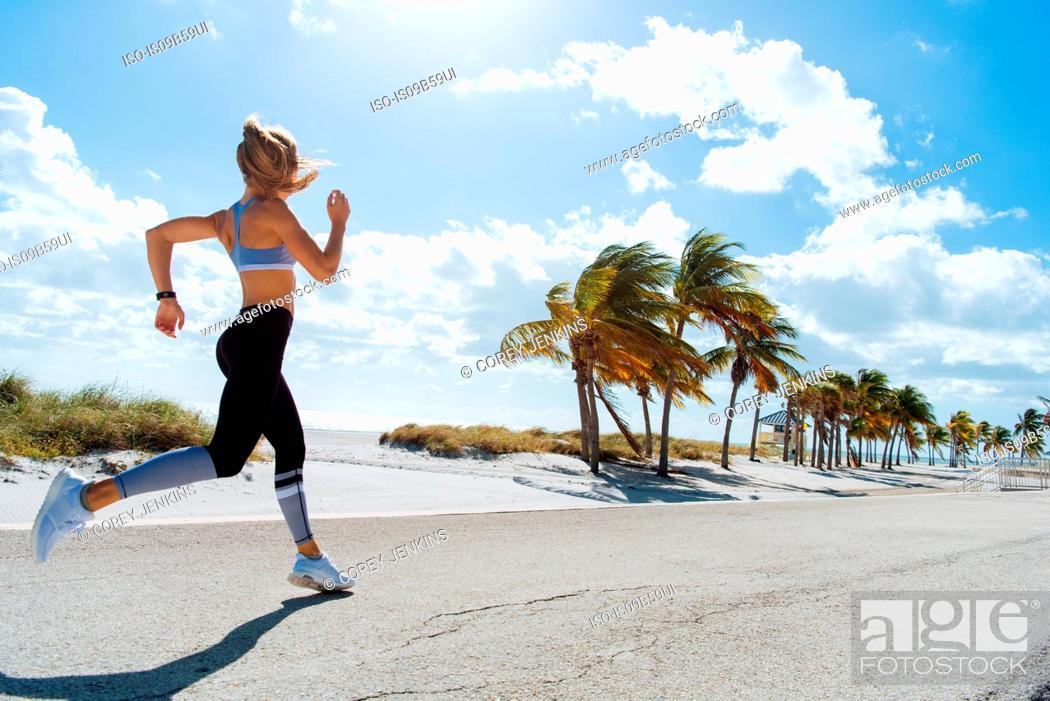 Stock Photo: Young female runner running at beach.