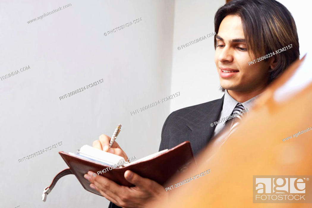 Stock Photo: Businessman writing in a personal organizer.