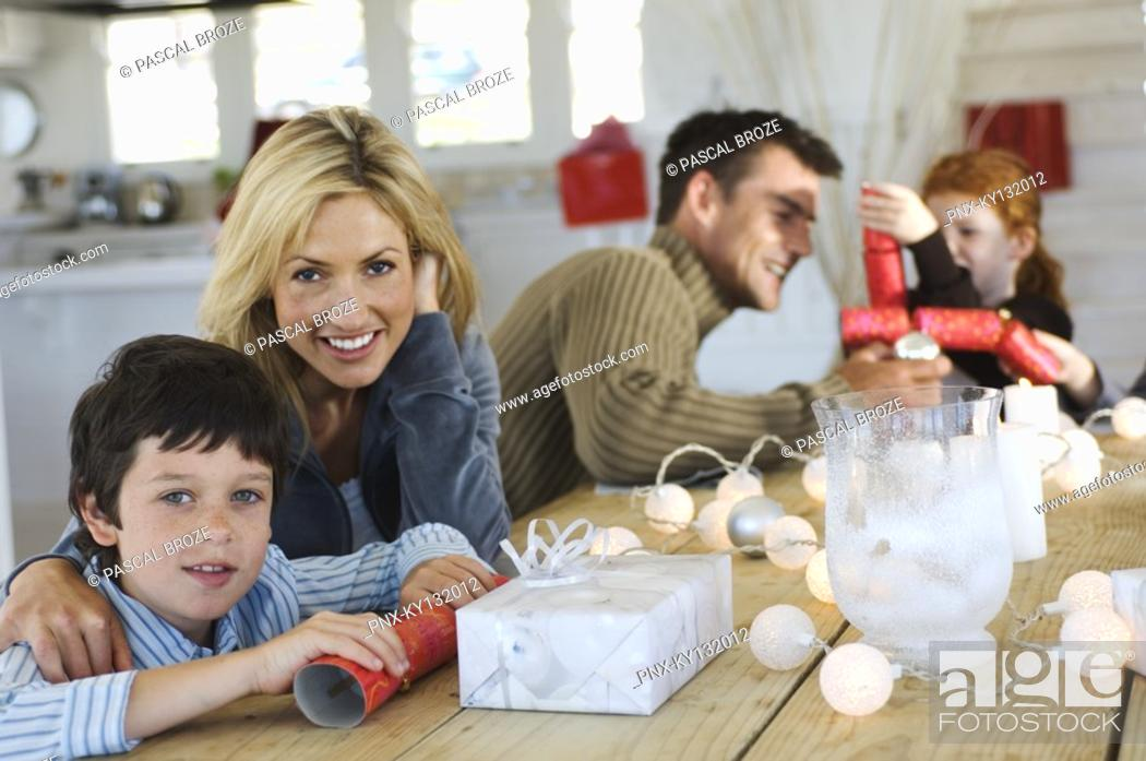 Stock Photo: Couple ad three children sitting around table, exchanging Christmas presents, indoors.