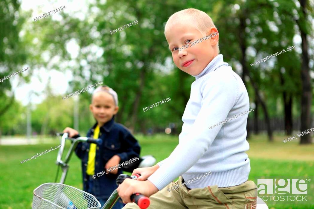 Stock Photo: Boy on a bicycle in the green park.