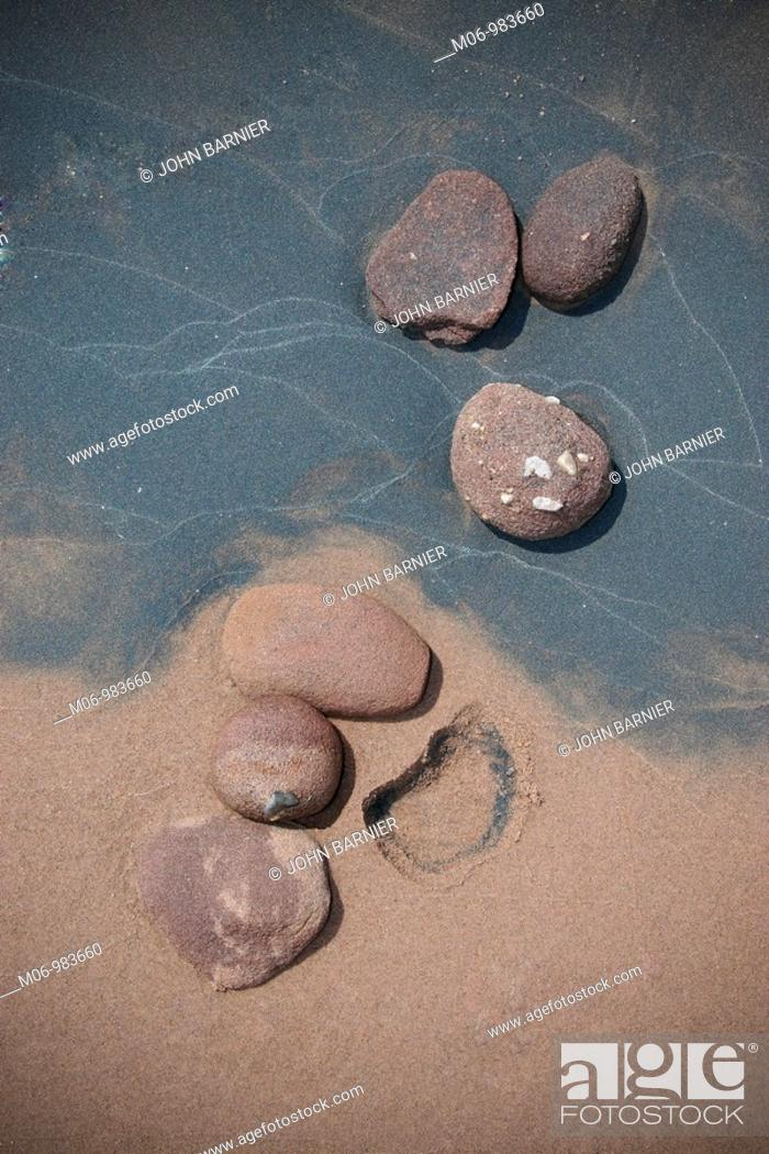 Imagen: A grouping of six rocks imbedded into beach sand with the impression of one rock missing.