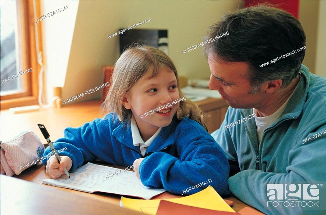 Stock Photo: father and daughter doing homework together.