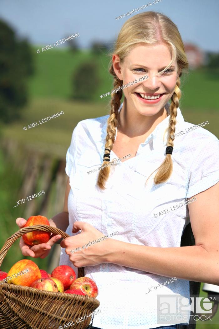 Stock Photo: blond woman holding basket with apples,.